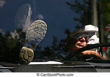 A lorry driver is sleeping on his truck. The gray shoes...