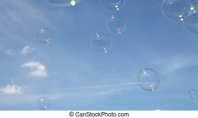 Soap bubbles are floating through the air against a blue...