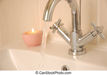 washbasin - tap running into washbasin with candle in...