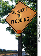Yellow Road Sign: 'Subject to Flooding' - Yellow warning...