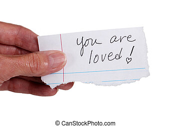 Hand holding note that reads You Are Loved - Close up of a...