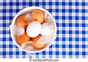 brown and white eggs, feathers in a bowl - brown and white...