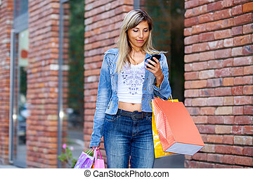 Woman with shopping bags and cellphone walking on street