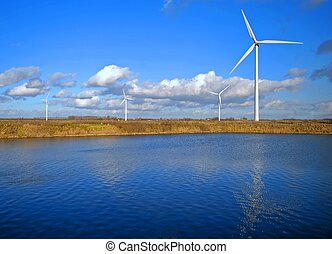 Wind Turbines and lake under a cloudy blue sky
