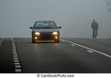 Car appearing through fog and cyclist riding in
