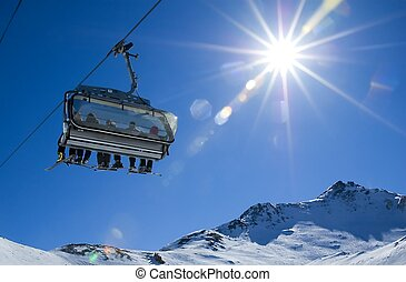 skiers in a chairlift backlit by the sun and spreading...
