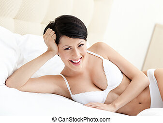 Woman in white bra is lying in the soft bed - Woman in white...