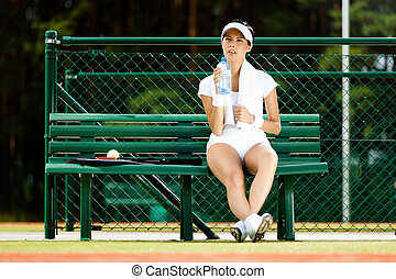 Female tennis player rests at the bench - Female tennis...