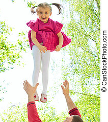 Father tossing up his daughter laughing in the park