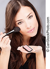make up with powder brush - pretty young woman doing make up...