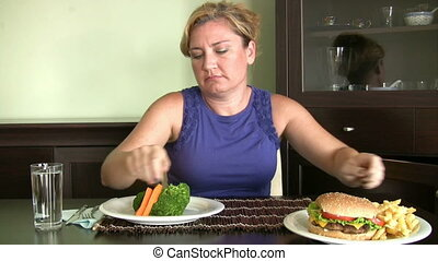 Dieting - Hungry women looking two plate and choosing one of...