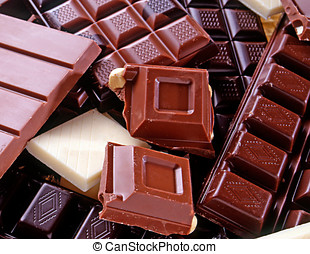 Variety of slab chocolate broken into squares with white...
