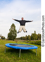 Man jumping on the trampoline seems higher tree