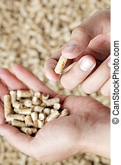 Wood Pellets - Man holding a wood pellet between his fingers...