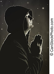 Hooded man praying to God