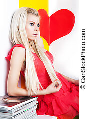 Sexy young female blonde posing in studio over red heart -...