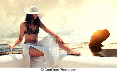 Fit beautiful woman in tropical beach dramatic cloudscape on...