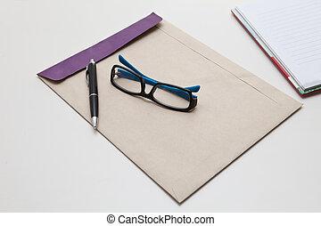 pen and glasses on brown envelope