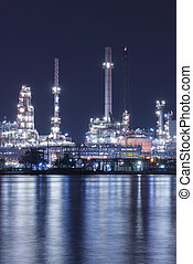 Oil refinery plant night scene nearby river in Thailand -...