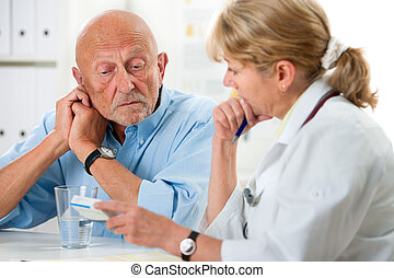 Medical exam - doctor talking to her male senior patient at...