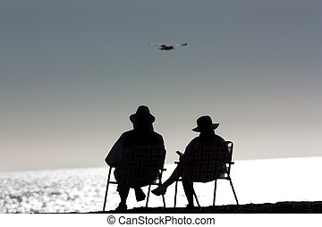 Senior Couple Relaxing at the Beach - Senior Couple Relaxing...