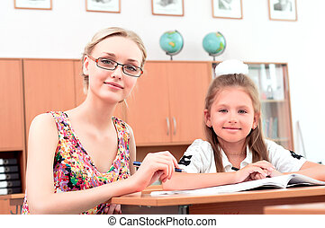 teacher sitting near pupil - teachers are engaged with...
