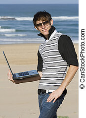 Working at the beach - Young professional male standing with...