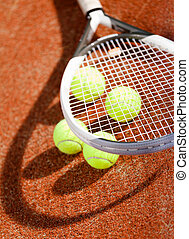 Close up of tennis racket and balls on the clay tennis court