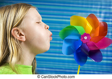 Pinwheel - Children with rainbow pinwheel on a striped blue...