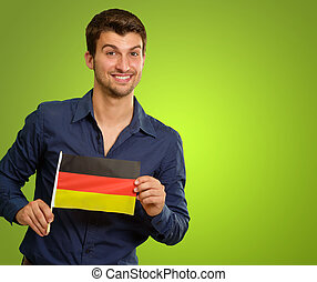 A Young Man Holding A German Flag On Green Background