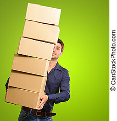 A Young Man Holding A Stack Of Cardboard Boxes On Green...