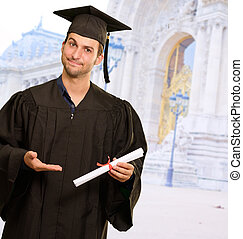 Young Man In Graduation Gown Holding Certificate, Outdoor