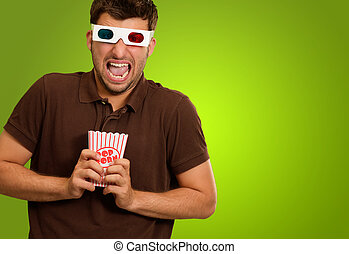 Young Man Wearing 3d Glasses And Holding Popcorn On A Green...