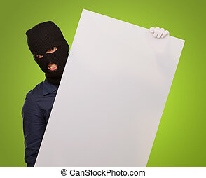 man with mask holding a blank card against a green...