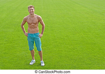 Fit young man on green playing field - Fit young man...