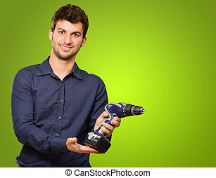 Man Holding Drill Machine On Green Background
