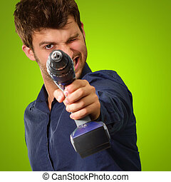 Man Aiming With Drill Machine On Green Background