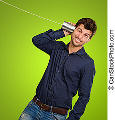 Man Listening From Tin Can Telephone against a green...
