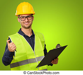 A Young Engineer Holding A Writing Pad On Green Background