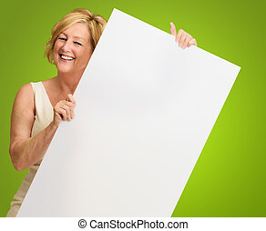 Happy Mature Woman Holding A Blank Billboard On Green...