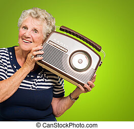 Senior Woman Listening Music On Radio Isolated On Green...