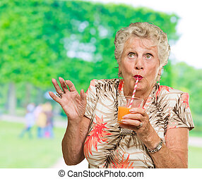 Senior Woman Drinking Orange Juice