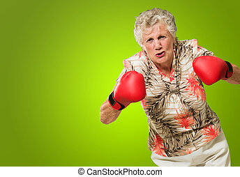 Angry Mature Woman Wearing Boxing Glove Isolated On Green...