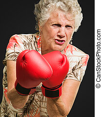 Angry Mature Woman Wearing Boxing Glove Isolated On Black...
