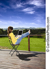 Vacation - Woman enjoying a beautiful day with a laptop on...