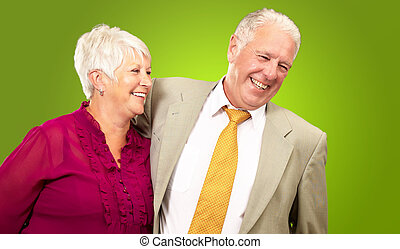 Portrait Of A Happy Senior Couple Isolated On Green...