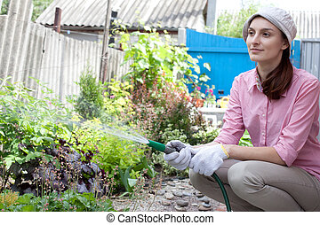 Young woman watering the garden bed