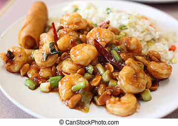 Plate of kung pao shrimp with rice and egg roll at a Chinese...