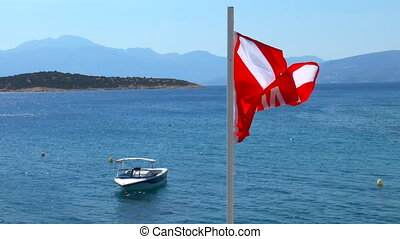 Waving Divers Alert Network DAN flag and Mirabello Bay near...