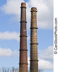 chimneys - two chimneys against the blue sky and clouds